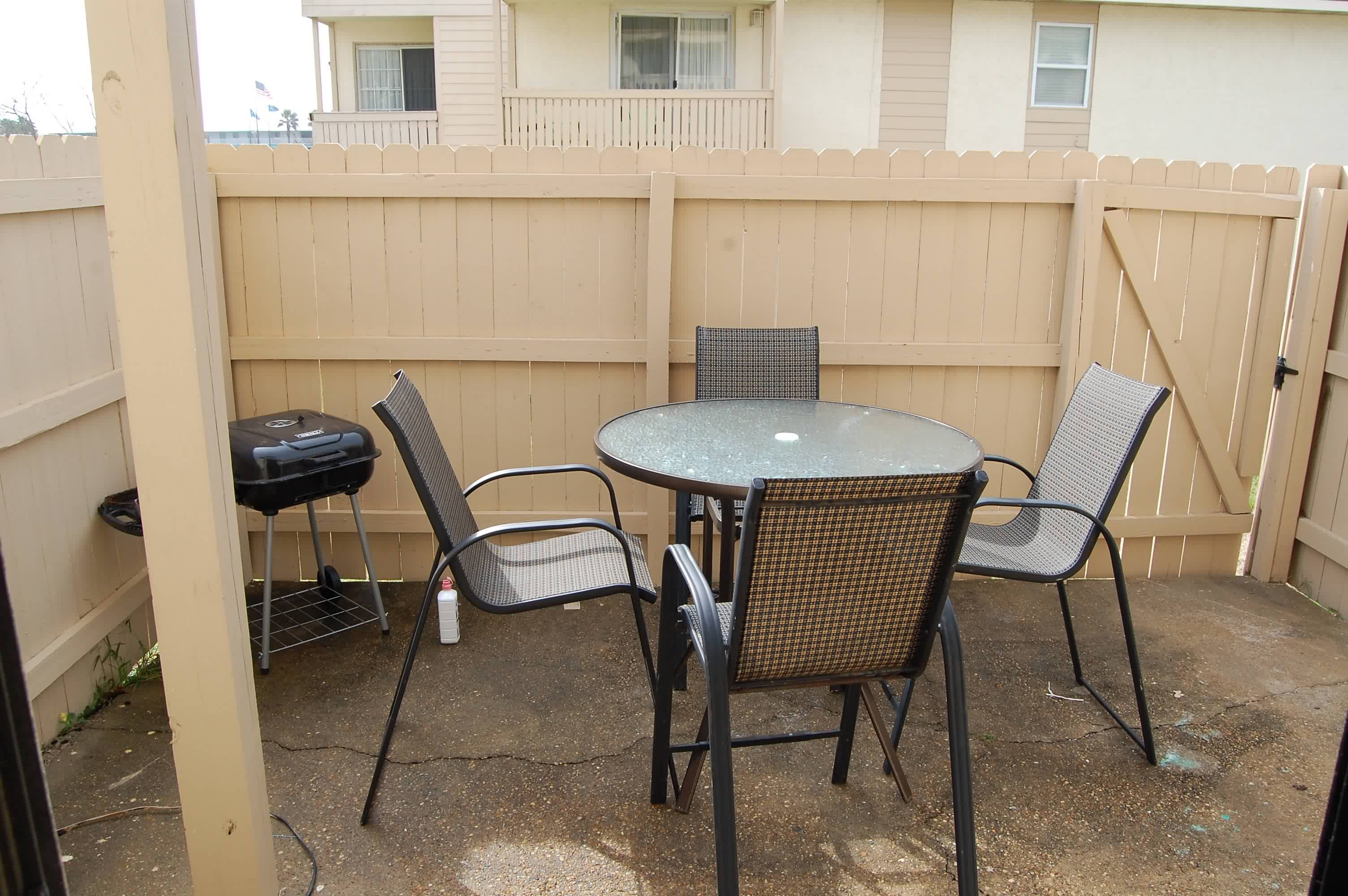 Enclosed patio with table, chairs, and grill